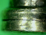 Damage to the serrations of a spool pin with serrated edges.